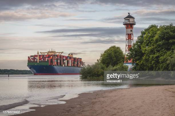 germany, hamburg, container ship on elbe river and wittenbergen lighthouse at sunset - エルベ川 ストックフォトと画像