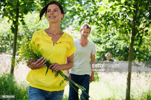 Germany, Hamburg, Couple in garden, woman holding bunch of flowers