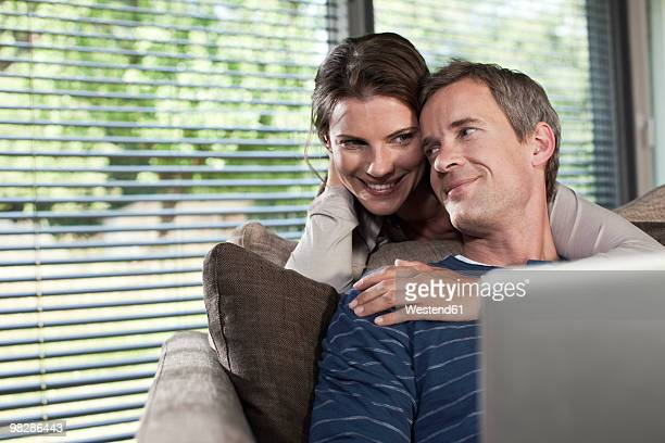 Germany, Hamburg, Couple in living room using laptop, smiling