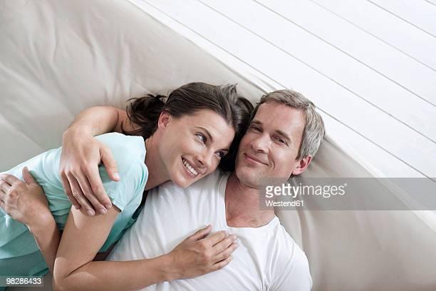 Germany, Hamburg, Couple lying on bed, overhead view