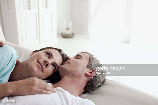 Germany, Hamburg, Couple lying on bed, woman looking up