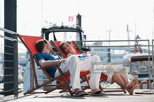 Germany, Hamburg, Couple relaxing in deck chair on floating home