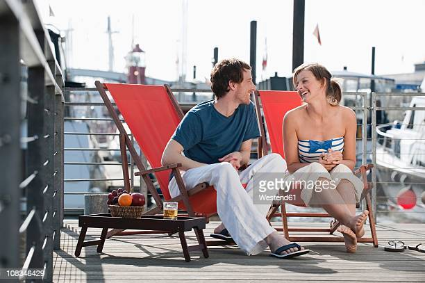 Germany, Hamburg, Couple relaxing in deck chair on floating home, smiling