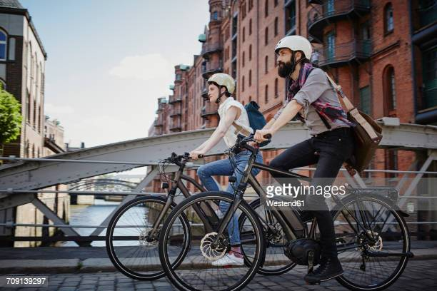 germany, hamburg, couple riding electric bicycles at old warehouse district - hamburg germany stock pictures, royalty-free photos & images
