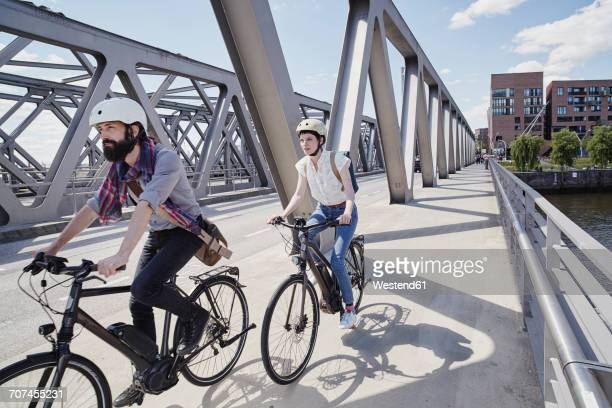 Germany, Hamburg, couple riding electric bicycles on a bridge