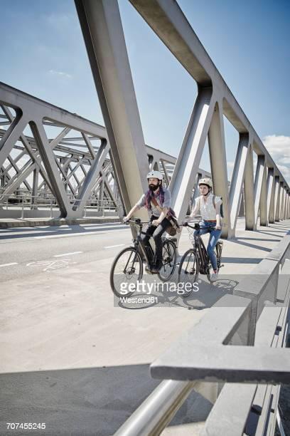 Germany, Hamburg, couple riding electric bicycles on a bridge