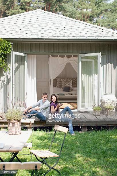 Germany, Hamburg, Couple sitting back to back on patio, smiling