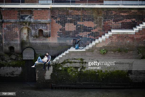 germany, hamburg, couple with electric bicycle relaxing at old warehouse district - hamburg stock-fotos und bilder