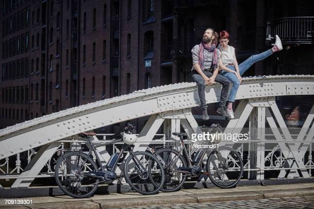 germany, hamburg, couple with electric bicycles sitting on railing of a bridge - hamburg stock-fotos und bilder