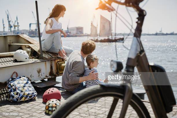 Germany, Hamburg, family having a break from a bicycle tour at River Elbe