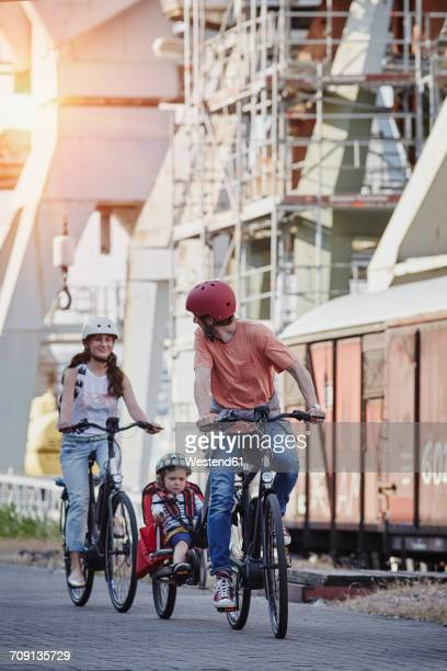Germany, Hamburg, family riding e-bikes at the harbor
