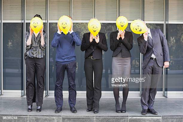 Germany, Hamburg, Five Business people standing in front of office building, hiding faces behind balloons