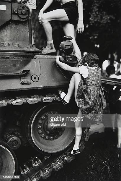 Germany Hamburg girl climbing on a military tank of the German Army