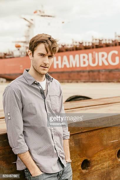 Germany, Hamburg, Hafencity, young man at harbor