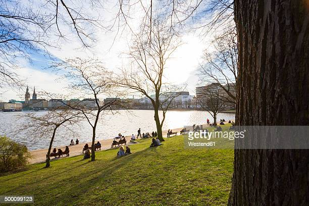 Germany, Hamburg, Inner Alster Lake in spring, people on meadow at lakeshore