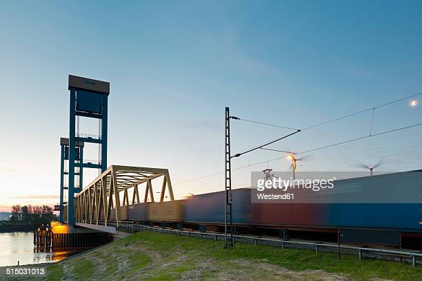 Germany, Hamburg, Kattwyk bridge, Train with containers, Wind wheels in the background