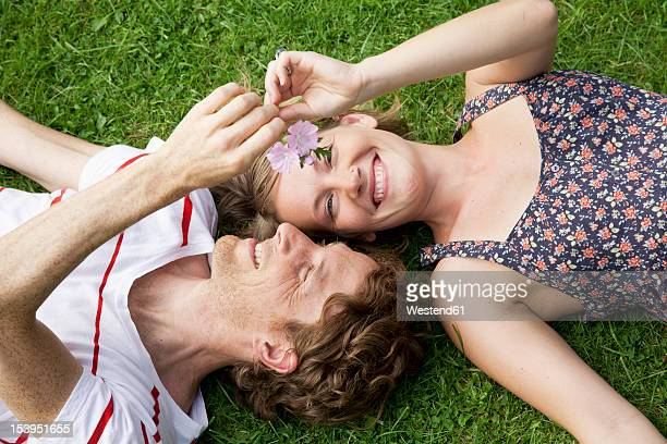 Germany, Hamburg, Man and woman lying on grass in allotment garden