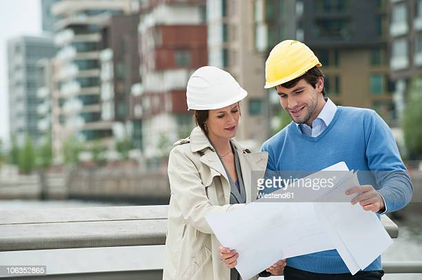 Germany, Hamburg, Man and woman with blueprint at harbour