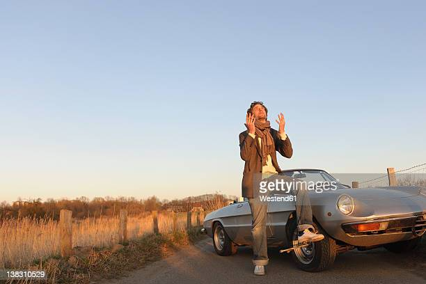 germany, hamburg, man changing tyre of classic cabriolet car - vintage auto repair stock pictures, royalty-free photos & images