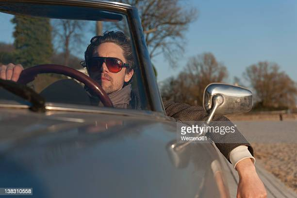 Germany, Hamburg, Man driving classic cabriolet car