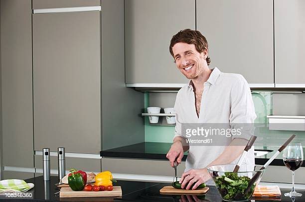 Germany, Hamburg, Man in kitchen cutting cucumber