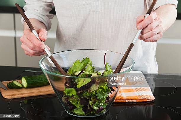 Germany, Hamburg, Man in kitchen mixing vegetable