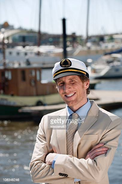 Germany, Hamburg, Man in suit with sailor cap, smiling