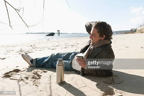 Germany, Hamburg, Man lying on sand with coffee flask near Elbe riverside