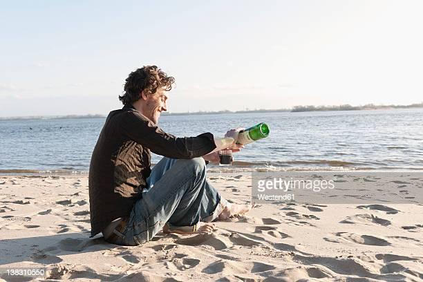 Germany, Hamburg, Man pouring wine in glass near Elbe riverside
