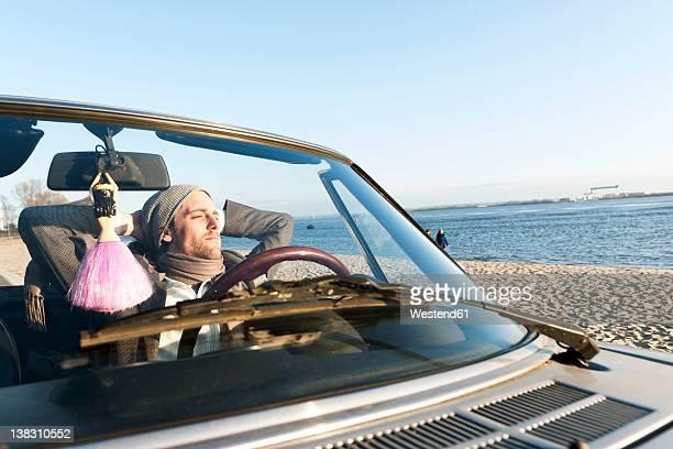 Germany, Hamburg, Man sitting in classic cabriolet car near Elbe riverside