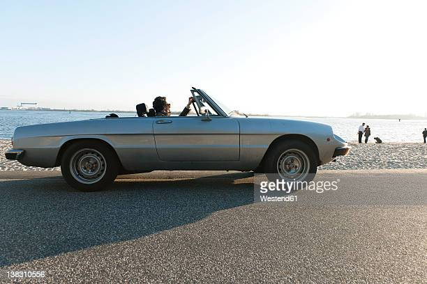 Germany, Hamburg, Man sitting in classic cabriolet car near Elbe riverside