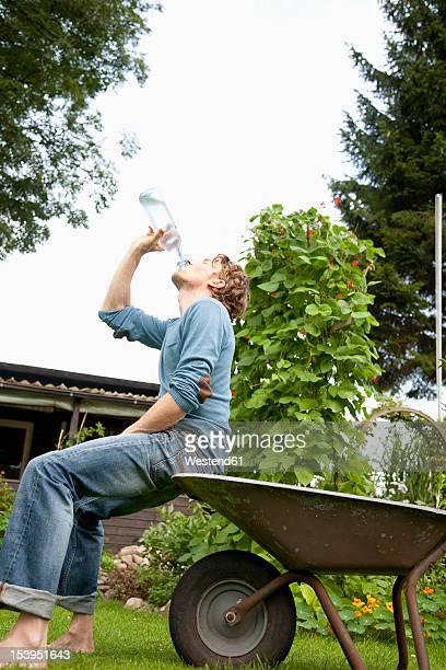 Germany, Hamburg, Man sitting on wheelbarrow and drinking water in allotment garden