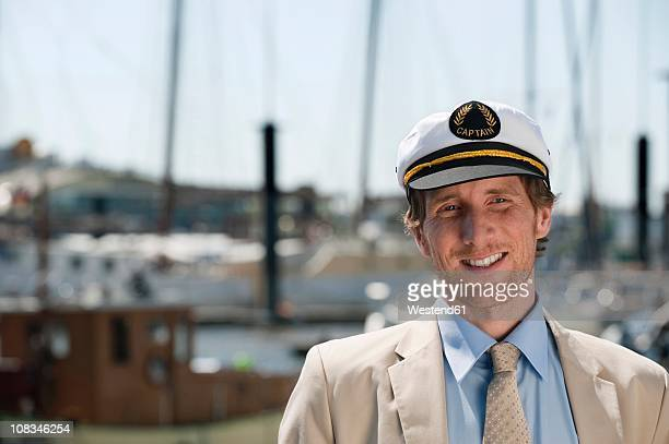 Germany, Hamburg, Man smiling with boat in background, close up