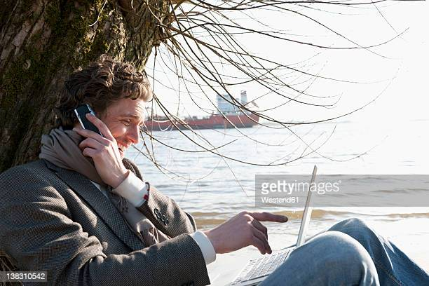 Germany, Hamburg, Man using laptop and cell phone near Elbe riverside with container ship in background