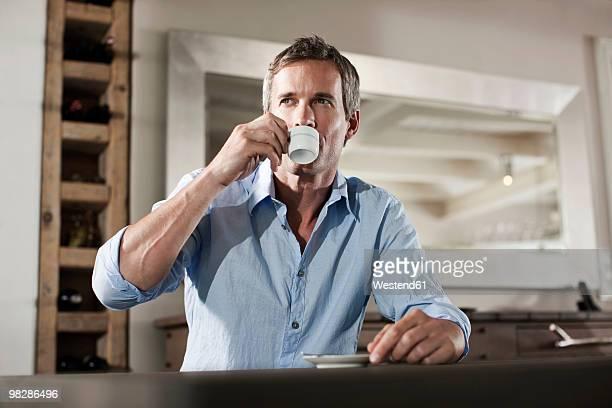 Germany, Hamburg, Mature man sitting at table drinking espresso