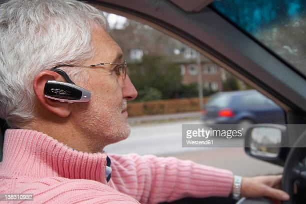 germany, hamburg, mature man using headset and driving taxi - bluetooth stock pictures, royalty-free photos & images