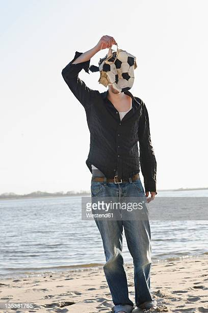 Germany, Hamburg, Mid adult man covering his face with torn football near Elbe river