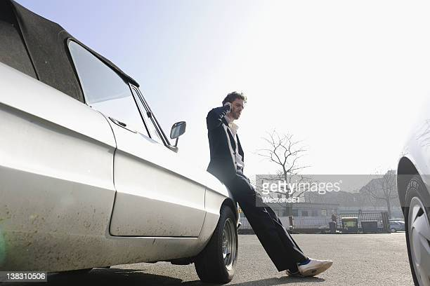 Germany, Hamburg, Mid adult man leaning on classic car and talking on mobile phone