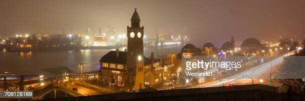 Germany, Hamburg, panoramic view of St. Pauli Landing Stages with port in the background at night