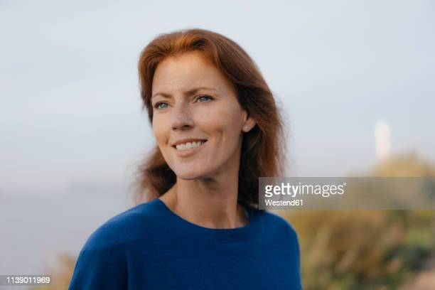 germany, hamburg, portrait of smiling woman at the elbe shore - older redhead stock pictures, royalty-free photos & images
