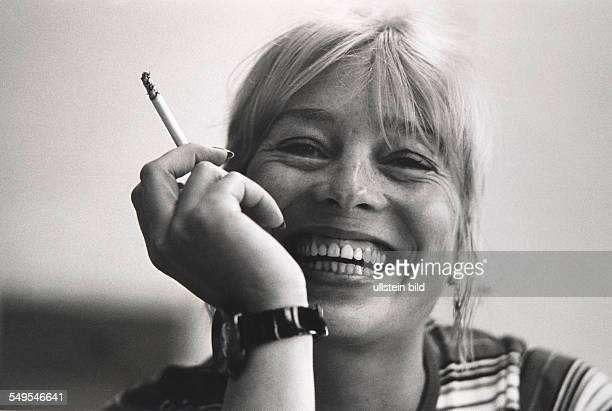 Germany Hamburg portrait of young blond woman smoking and laughing