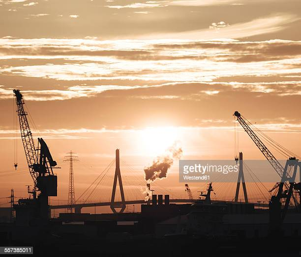 germany, hamburg, silhouettes of harbour cranes at sunset, koehlbrand bridge in the background - köhlbrandbrücke stock photos and pictures