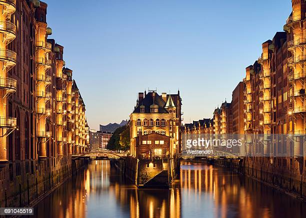 Germany, Hamburg, Speicherstadt, lighted old buildings with Elbe Philharmonic Hall in the background