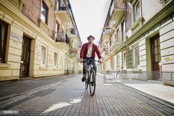 Germany, Hamburg, St. Pauli, Man riding bicycle in he city