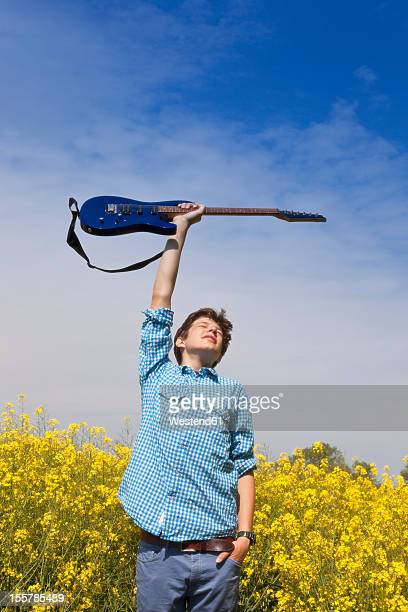 Germany, Hamburg, Teenage boy standing in canola field with electric guitar