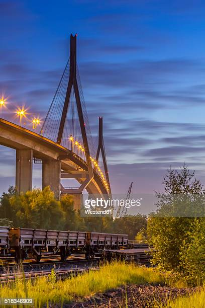 germany, hamburg, train cars in front of the koehlbrand bridge in the port of hamburg in the evening - köhlbrandbrücke stock photos and pictures