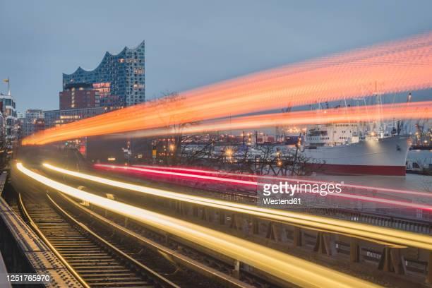 germany, hamburg, train light trails along elevated railway track at dusk - hamburg stock-fotos und bilder