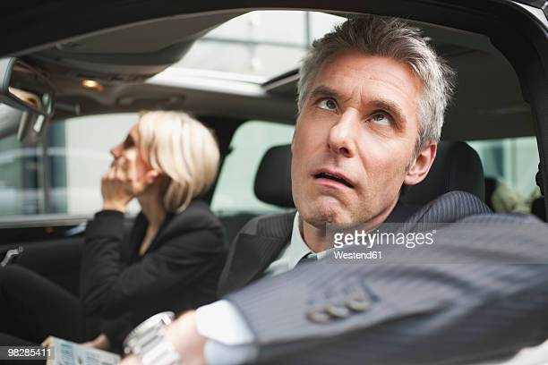 Germany, Hamburg, Businessman sitting in car looking up