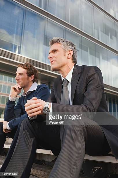 Germany, Hamburg, Businessmen sitting on steps in front of office building