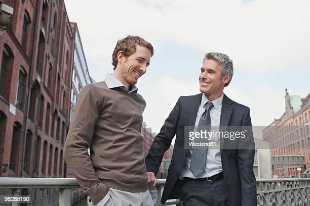 germany, hamburg, two businessmen talking - côte à côte photos et images de collection